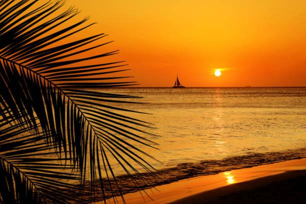 orange colored shiny seascape with sailboat over sunset sky stock photo