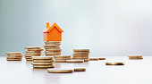 istock Orange Colored Toy House Sitting over Coin Stacks: Insurance And Real Estate Concept 1255580364
