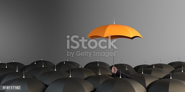 Business Man holding orange colored umbrella between the black umbrellas