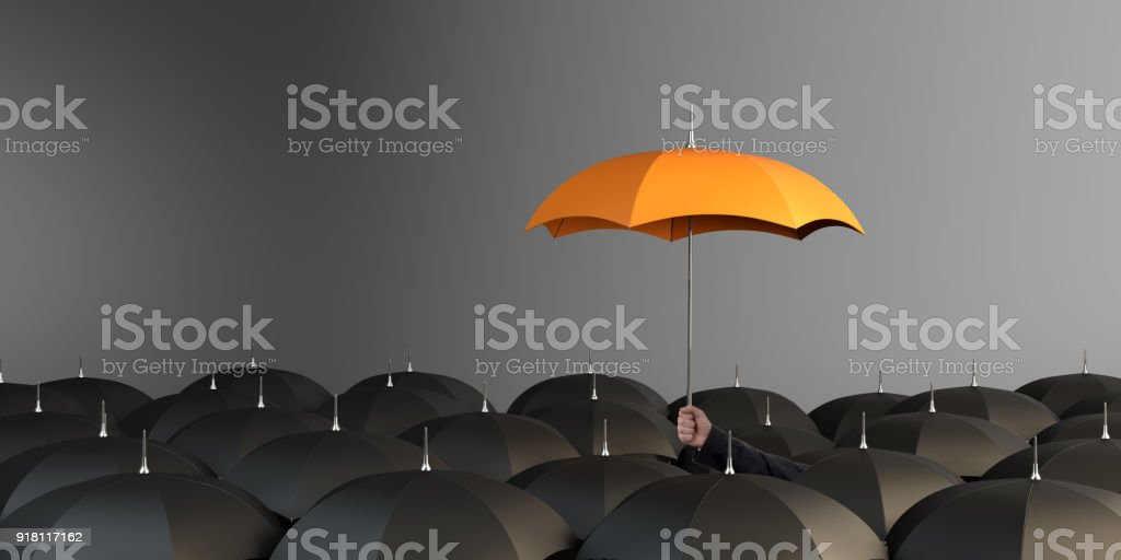 Orange Colored Umbrella Between The Black Umbrellas stock photo