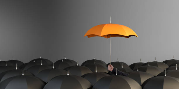 orange colored umbrella between the black umbrellas - protection stock photos and pictures