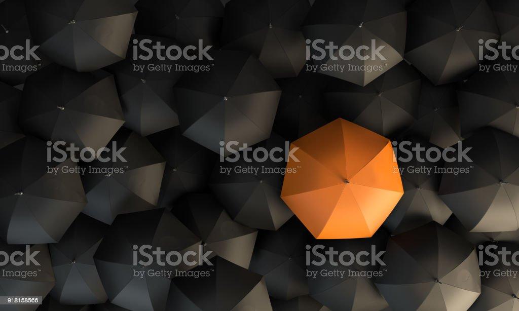 Orange Colored Umbrella Between The Black Umbrellas stock photo