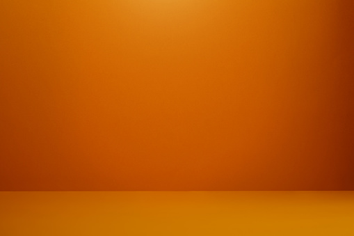 Orange colored wall and floor with a soft shadow at the corner