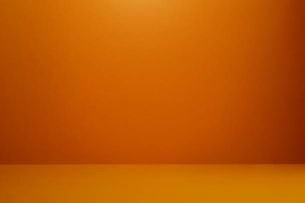 Orange colored wall and floor with a soft shadow at the corner stock photo