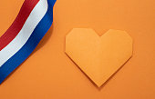 An orange paper heart on an orange background with a ribbon in red white and blue. Room for copy.