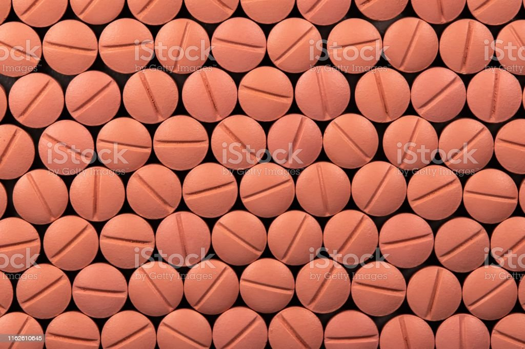 Orange colour round pills on black background with selective focus....