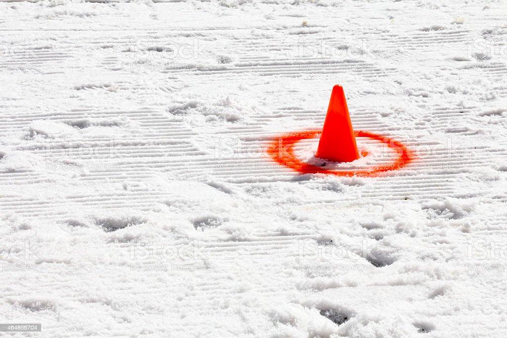 Orange cone with spray paint circle on snow stock photo