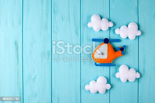 istock Orange craft helicopter and clouds on blue wooden background with copyspace. Felt handmade toys. Empty space for text. Top view. 869302782