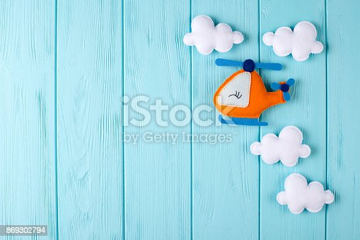 istock Orange craft helicopter and clouds on blue wooden background with copyspace. Felt handmade toys. Empty space for text. Top view. 869302794