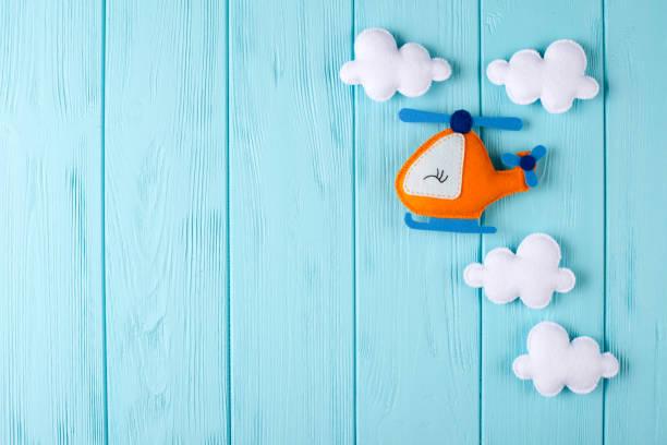 orange handwerk hubschrauber und wolken am blauen hölzernen hintergrund mit exemplar. handgemachte spielsachen fühlte. leeren raum für text. ansicht von oben. - filzunterlage stock-fotos und bilder