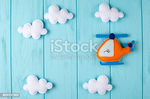 istock Orange craft helicopter and clouds on blue wooden background with copyspace. Felt handmade toys. Empty space for text. Top view. 869302860