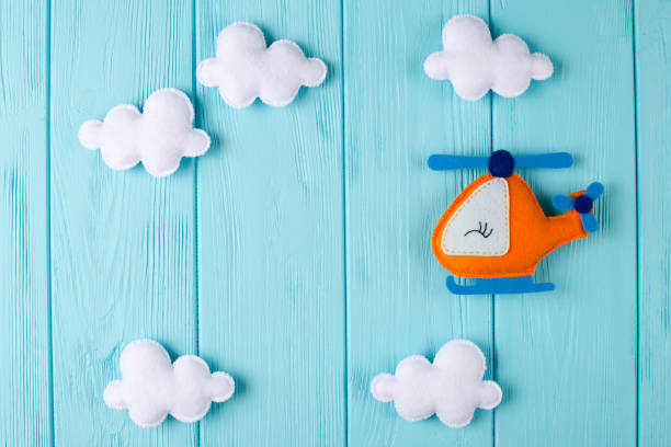 orange craft helicopter and clouds on blue wooden background with copyspace. felt handmade toys. empty space for text. top view. - felt textile stock pictures, royalty-free photos & images