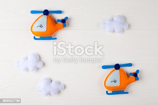istock Orange craft helicopter and clouds on white wooden background with copyspace. Felt handmade toys. Empty space for text. Top view. 869302796