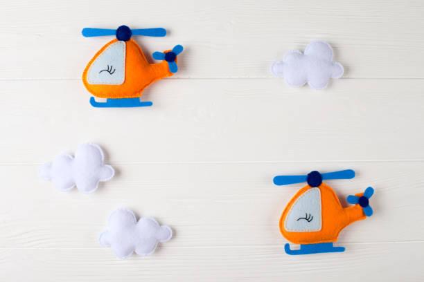 orange handwerk hubschrauber und wolken auf weißem holz hintergrund mit exemplar. handgemachte spielsachen fühlte. leeren raum für text. ansicht von oben. - filzunterlage stock-fotos und bilder