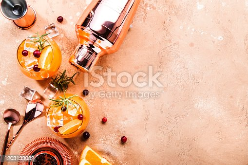 Orange Cranberry Rosemary and Vodka cocktail, copper bar tools, beige background, hard light, top view