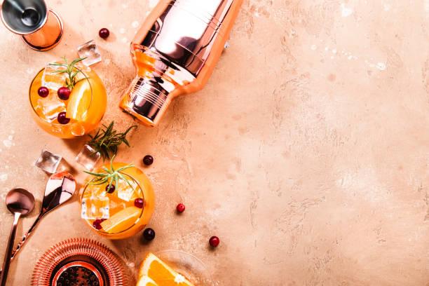 oranje cranberry rosemary en wodka cocktail, koperen bar tools, beige achtergrond, hard licht, top view - cocktail stockfoto's en -beelden