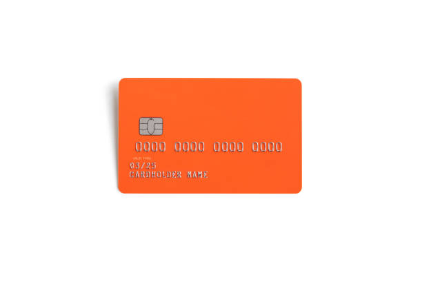orange credit card isolated on a white background with natural shadow - credit card стоковые фото и изображения