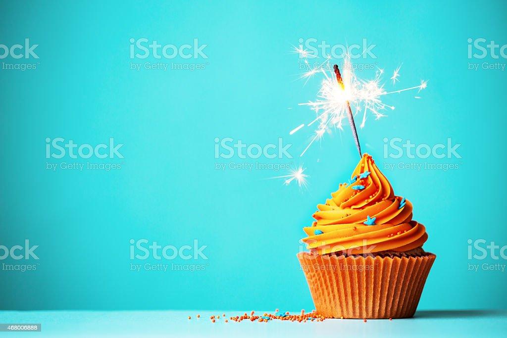 Orange cupcake with sparkler - 免版稅2015年圖庫照片