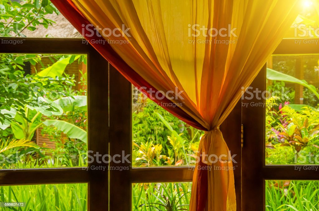 orange curtain on window in front of tropical garden royalty-free stock photo