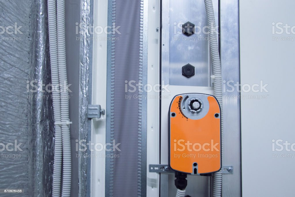 Orange damper actuator installed on the industrial ventilation unit body, front view stock photo