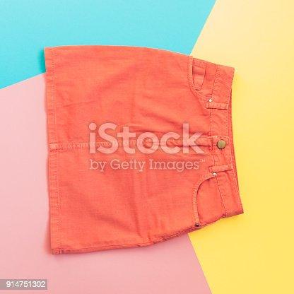 640200626istockphoto orange denim skirt on pink, yellow and blue 914751302
