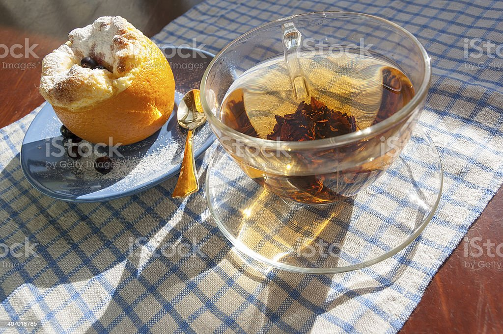 Orange dessert and  glass cap of tea with golden teaspoon royalty-free stock photo