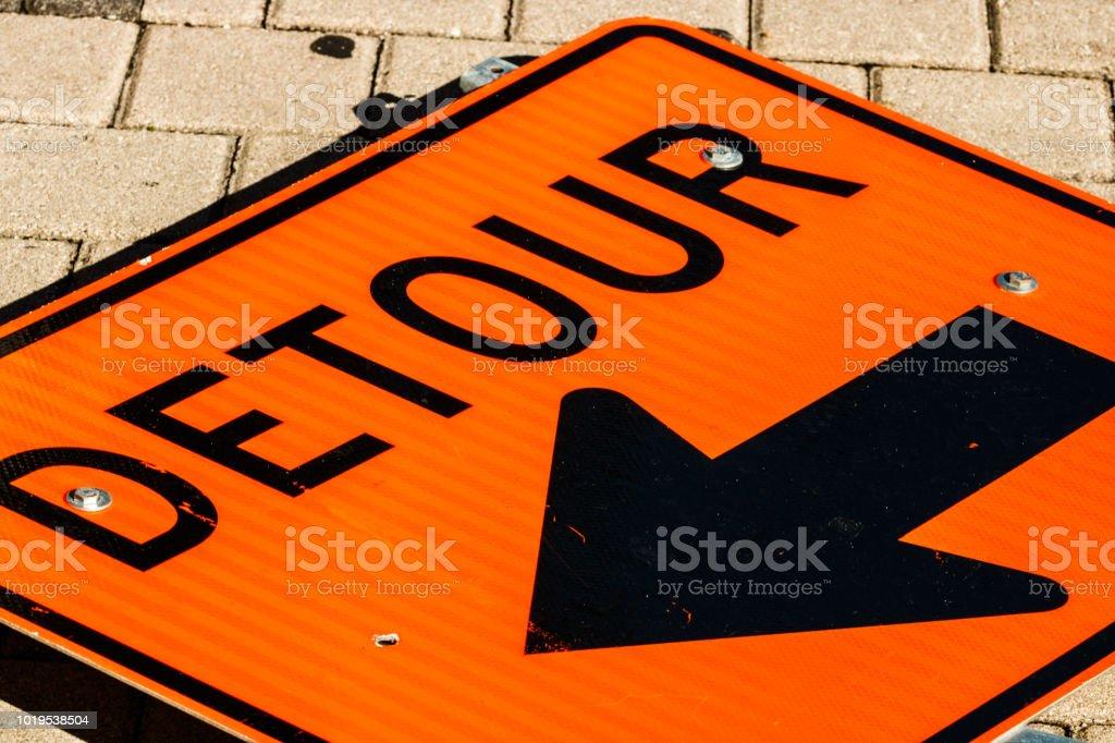 Orange detour sign dropped on the street. stock photo