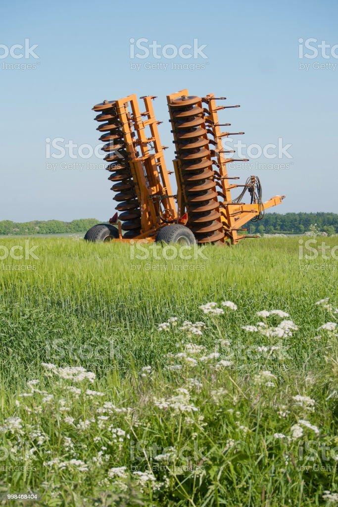 Orange Disc Harrow in field stock photo