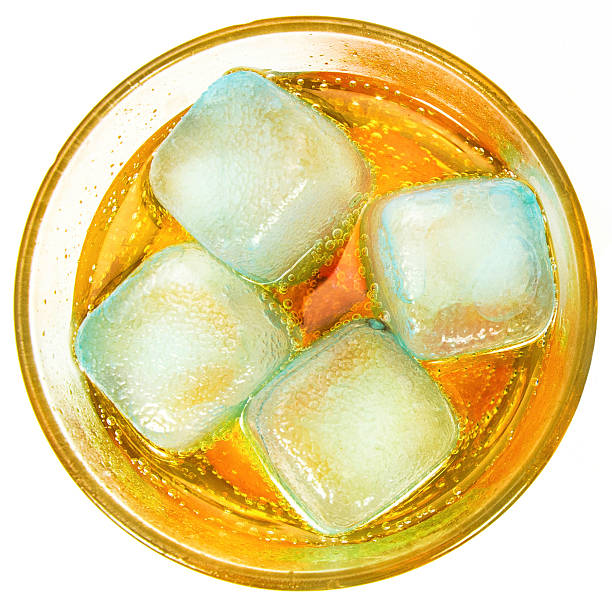 Orange drink in a glass with ice stock photo