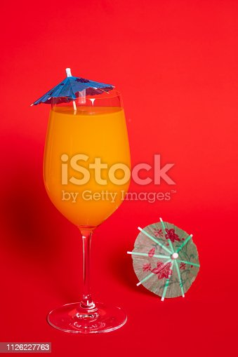 istock Orange Drink in Wine Glass Against Red II 1126227763