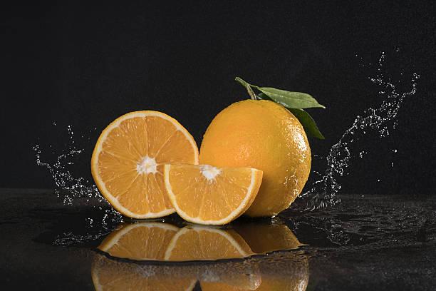 orange duo with leafs  water splash black background. - tropfenblatt tisch stock-fotos und bilder