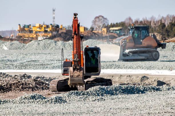 Orangefarbener Bagger und gelber Bulldozer baggern Trümmer beim Straßenbau – Foto