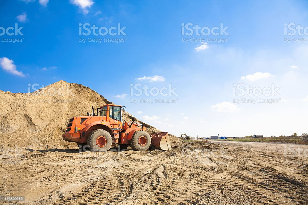 Orange excavator on a construction site royalty-free stock photo