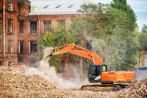 Orange excavator working on the ruins of a demolished building. Cleaning the rubble, building demolition and clearing site theme image