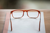 Orange eye glasses with white notebook on wooden table, Bokeh  background, Close up & Macro shot, Selective focus, Stationery concept
