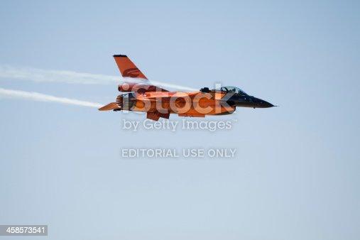 istock Orange F16 fighter jet against blue sky. 458573541