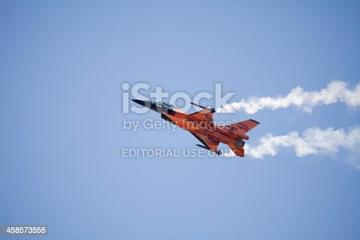 istock Orange F16 fighter jet against blue sky. 458573555