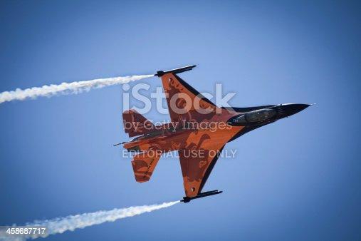 istock Orange F16 fighter jet against blue sky. 458687717