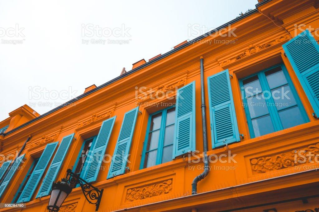 orange facade with blue decor windows stock photo