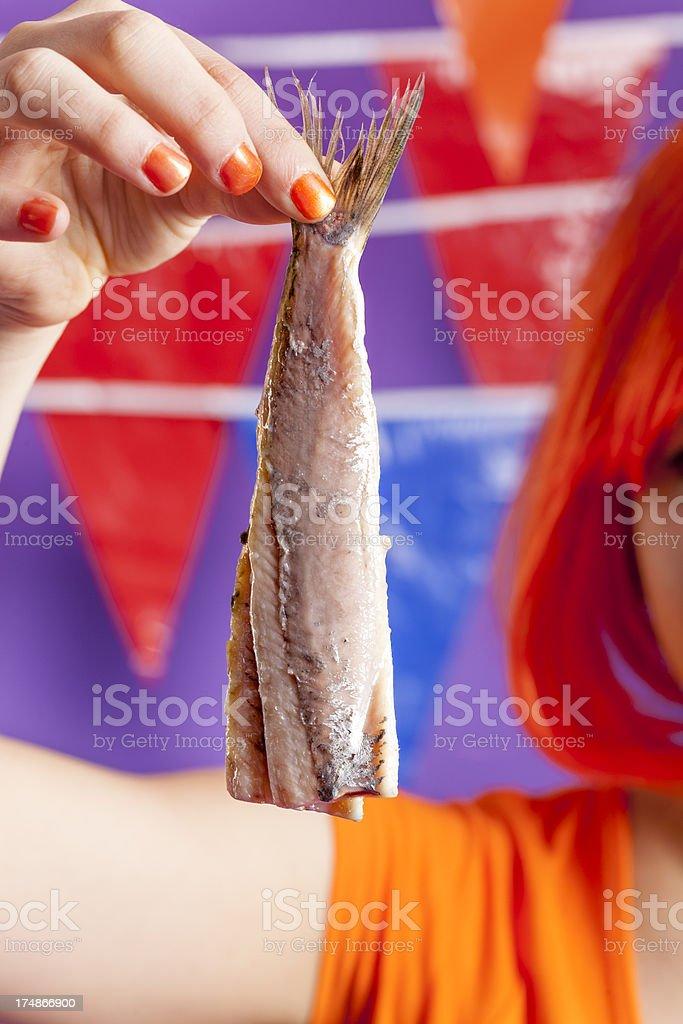 Orange fan eating herring royalty-free stock photo