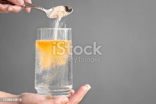 A person pouring orange powder into a glass of water with copyspace.