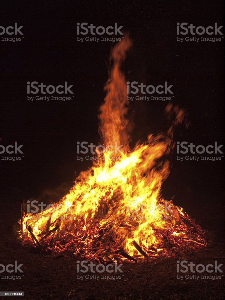 Fierce orange flames leaping up from a large outdoor wood bonfire.