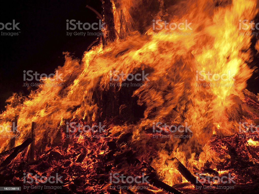 Orange flames leaping up from a large outdoor wood bonfire. royalty-free stock photo