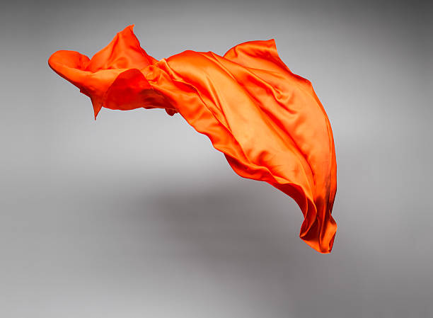 orange flying fabric orange flying fabric - art object, design element floating fabric stock pictures, royalty-free photos & images