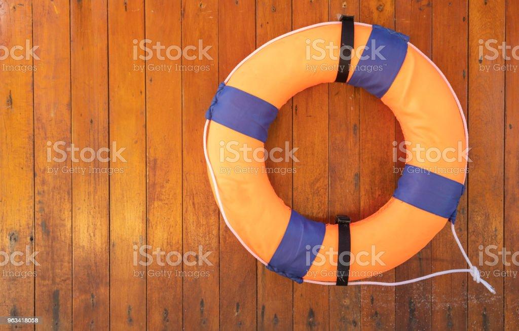 Orange foam life buoy on wood wall - Zbiór zdjęć royalty-free (Bez ludzi)