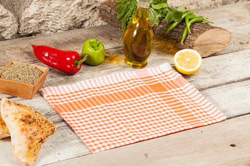 orange folded tablecloth over bleached wooden table