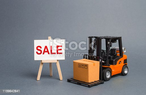 1155852718istockphoto Orange forklift truck carries a cardboard box and a stand with a word sale. growth of sales. big discounts on goods of the outgoing season. commodity exchange with other countries. Attracting buyers 1159642641