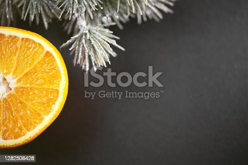 Close-up photography of an orange fruit and snowy pine needles with copy space and black background. Perfectly usable for all elegant winter subjects.