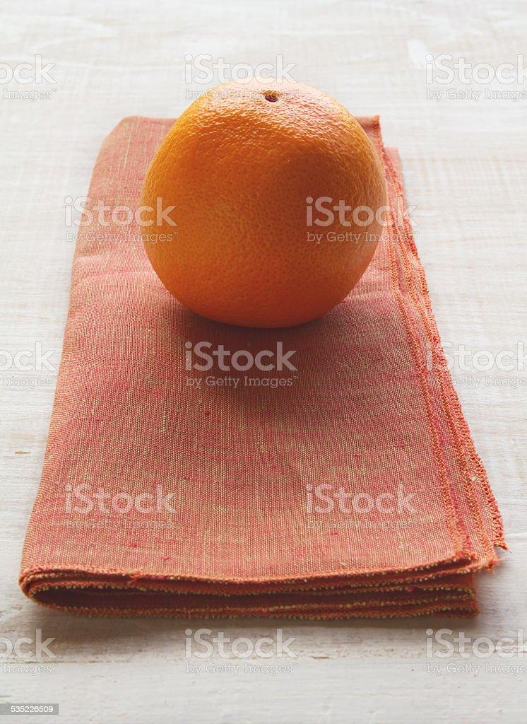 Orange fruit on a burnt orange colored napkin placemat stock photo
