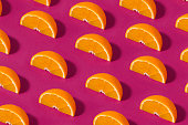 Fruit pattern with half slices of orange fruit on purple background